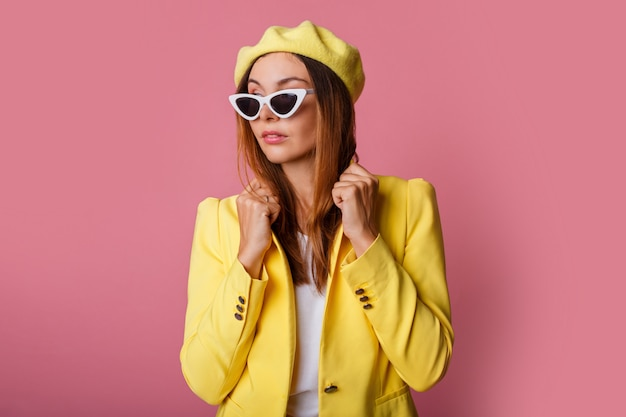 Feche o retrato da moda da mulher elegante de terno amarelo e boina.