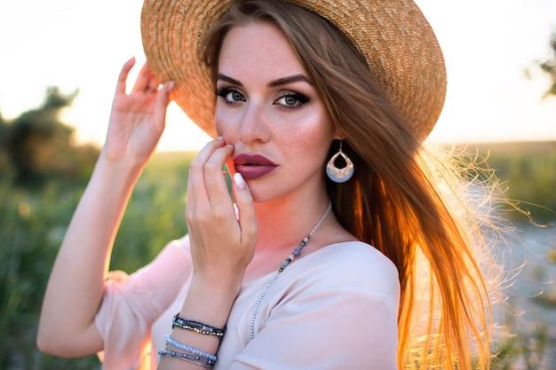 Feche o retrato da moda da mulher loira sensual, maquiagem brilhante, joias da moda, estilo boho, efeito de filme, posando ao ar livre.