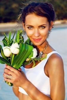 Feche o retrato da moda da noiva linda com maquiagem natural fresca e top branco simples, posando com buquê de lótus exótico ao pôr do sol na praia.