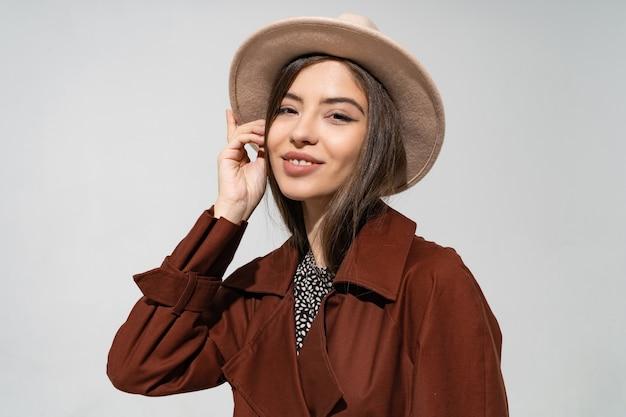 Feche o retrato da moda de estúdio interno de uma mulher linda em um elegante casaco marrom de inverno e chapéu preto