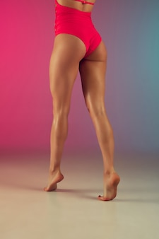Feche o retrato da moda de jovem em forma e mulher esportiva em elegantes trajes de banho rosa
