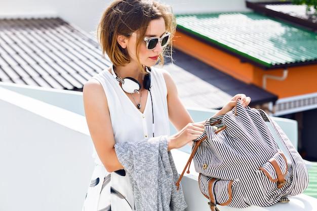 Feche o retrato da moda de uma mulher bonita jovem hippie, procurando algo em sua mochila, caminhando e se divertindo no telhado, roupa de estilo elegante de rua.