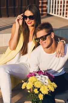 Feche o retrato da moda do jovem casal alegre elegante apaixonado posando ao ar livre na rua, sorrindo, rindo, abraçando e aproveitando o tempo juntos. cores quentes e ensolaradas. humor romântico.