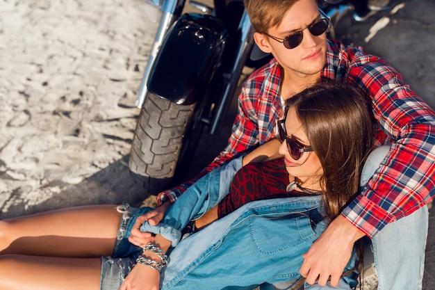 Feche o retrato da moda. elegante casal apaixonado posando perto de bicicleta na praia ensolarada.