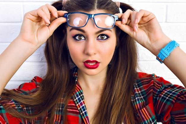 Feche o retrato da moda estilo de vida da mulher jovem hippie com maquiagem brilhante e dois rabos de cavalo engraçados, surpreendeu as emoções positivas.