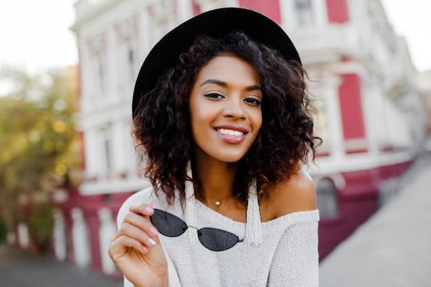 Feche o retrato da moda mulher negra com cabelos afro elegantes posando ao ar livre. meio urbano. usando óculos escuros pretos, chapéu e brincos brancos. acessórios da moda. sorriso perfeito.
