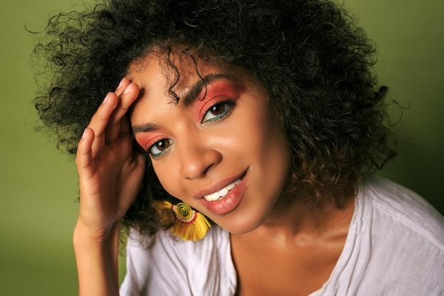 Feche o retrato da mulher africana com colorido brilhante; maquiagem posando