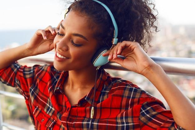 Feche o retrato da mulher americana, apreciando a música adorável por fones de ouvido, vestido com camisa quadriculada, de pé no telhado. fundo de paisagem urbana.