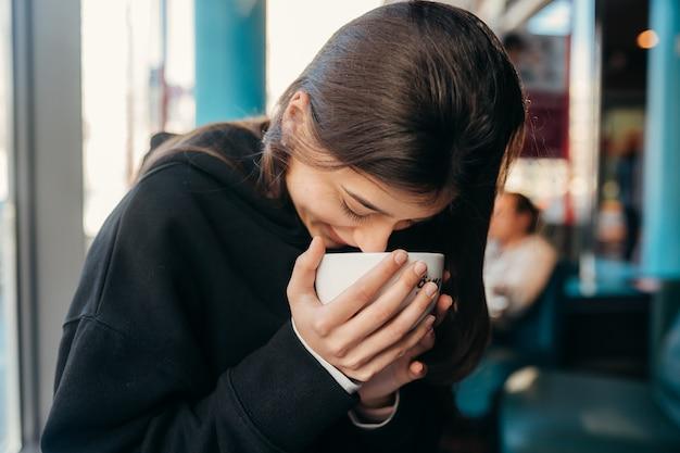 Feche o retrato da mulher bonita bebendo café.