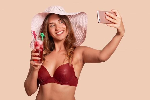 Feche o retrato da mulher caucasiana atraente, tendo selfie, mantendo o cocktail fresco na mão. mulher jovem lindo maiô vermelho e chapéu de palha posando novamente parede bege studio.