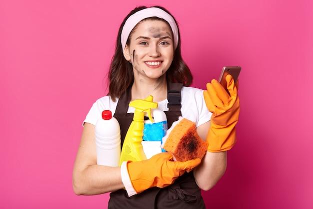 Feche o retrato da mulher de limpeza doce alegre na camiseta casual branca, avental marrom e faixa de cabelo, mantém a esponja, o telefone e os detergentes de limpeza, isolados sobre a parede rosa, fazendo trabalhos domésticos.