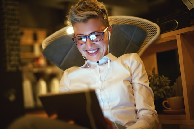 Feche o retrato da mulher de negócios bem sucedida sorridente elegante cabelo curto com óculos, verificando resultados da empresa em uma cadeira com um tablet e fones de ouvido na sala de estar à noite