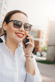 Feche o retrato da mulher de negócios morena mulher elegante em óculos de sol usando móveis