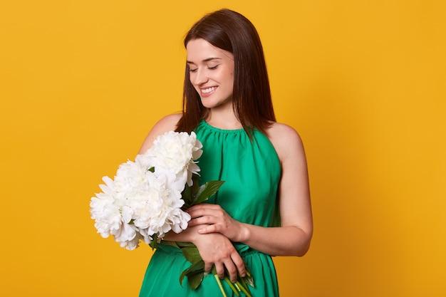 Feche o retrato da mulher elegante atraente na data em elegante vestido verde na parede amarela segurando o buquê de flores de peônia, tem expressão facial agradável, cai feliz. conceito de amor