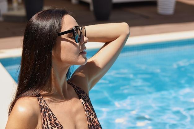 Feche o retrato da mulher romântica sonhadora posando sobre água limpa, relaxando perto da piscina, tocando o cabelo com a mão, olhando de lado, usando óculos de sol elegantes. conceito de lazer.