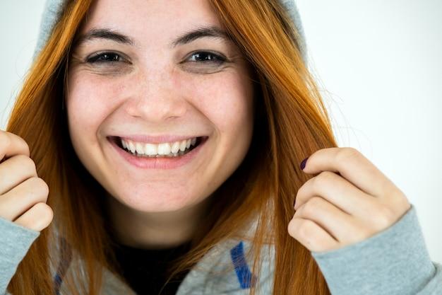 Feche o retrato da mulher ruiva jovem sorridente feliz vestindo pulôver quente com capuz.