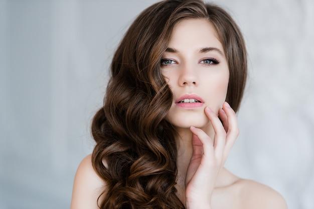 Feche o retrato da mulher sorridente linda noiva com cabelo longo encaracolado, posando em vestido de noiva no interior e sorrindo. retrato interior de beleza.