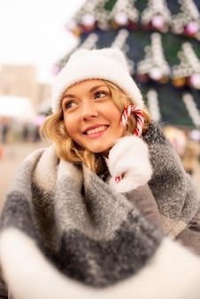 Feche o retrato da rua da bela jovem sorridente na festiva feira de natal. senhora vestindo roupas de malha elegantes clássicas de inverno. modelo olhando para a câmera.