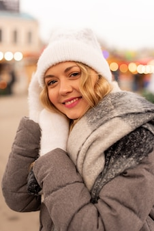 Feche o retrato da rua da bela jovem sorridente na festiva feira de natal. senhora vestindo roupas de malha elegantes clássicas de inverno.