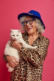 Feche o retrato da vovó feliz e enrugada na moda com um lindo gato