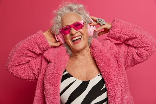Feche o retrato da vovó feliz e enrugada na moda usando meia-calça rosa e casaco