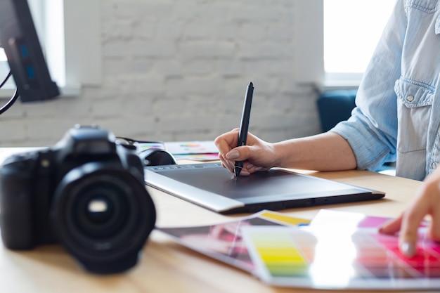 Feche o retrato das mãos do designer gráfico retocando imagens usando a mesa digitalizadora no programa especial. laptop, monitor e paleta de cores. retocador de local de trabalho em estúdio fotográfico. agência de criação.