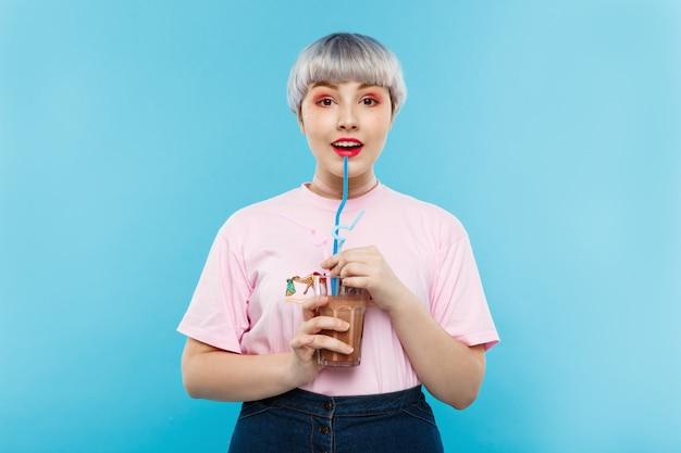 Feche o retrato de alegre sorridente linda garota dollish com cabelo violeta curto curto em camiseta rosa, bebendo suco sobre parede azul