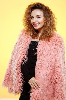 Feche o retrato de alegre sorridente menina morena encaracolada com casaco de pele rosa sobre parede amarela