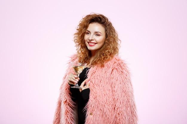 Feche o retrato de alegre sorridente menina morena linda com casaco de pele rosa, segurando o copo de cocktail sobre parede branca