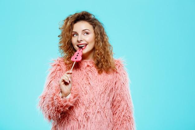 Feche o retrato de alegre sorridente menina morena linda encaracolada em pirulito de casaco de pele rosa sobre parede azul
