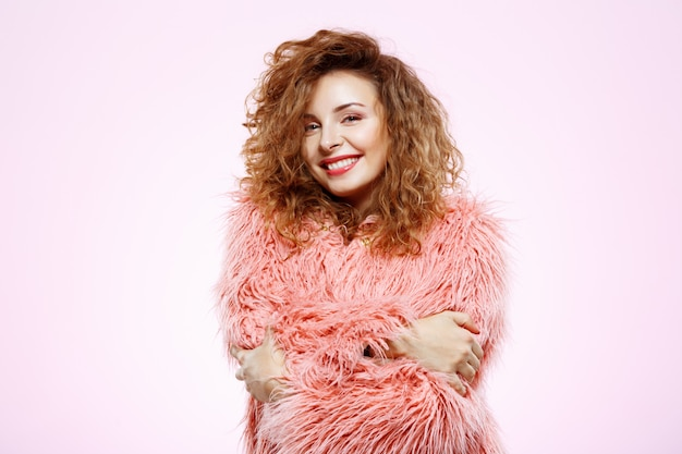 Feche o retrato de alegre sorridente menina morena morena bonita com casaco de pele rosa sobre parede branca