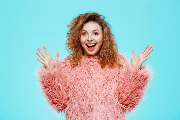 Feche o retrato de alegre surpresa sorridente menina morena morena bonita com casaco de pele rosa sobre parede azul