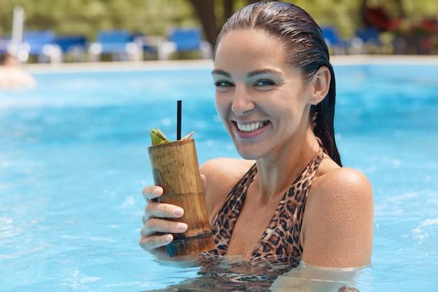Feche o retrato de atraente energético doce jovem bonito feminino sorrindo sinceramente, segurando o copo de madeira com coquetel frio, smimming sozinho. pessoas e relaxar o conceito.