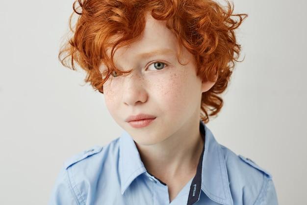 Feche o retrato de criança linda com cabelo ruivo cacheado e olhos cinzentos, olhando com expressão séria e relaxada.