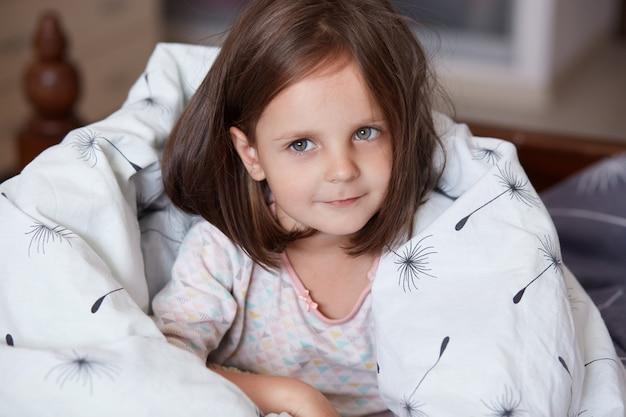 Feche o retrato de doce menina de cabelos escura, sentado em sua cama e embrulhado o cobertor branco, olhando para a câmera e sorrindo enquanto estiver em casa na sala aconchegante, criança feminina, vestindo pijama branco.