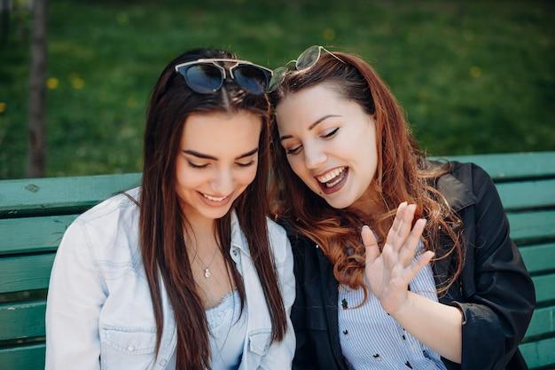 Feche o retrato de duas belas mulheres se divertindo, rindo, enquanto está sentado na praia na hora do almoço.