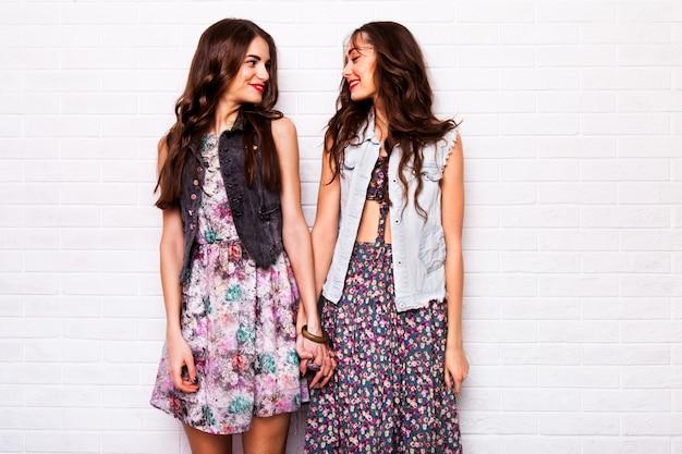 Feche o retrato de duas melhores amigas hipster bonita usando vestido colorido boho, jaqueta elegante e enfeites. as meninas sorriem, divirtam-se contra a parede branca urbana.