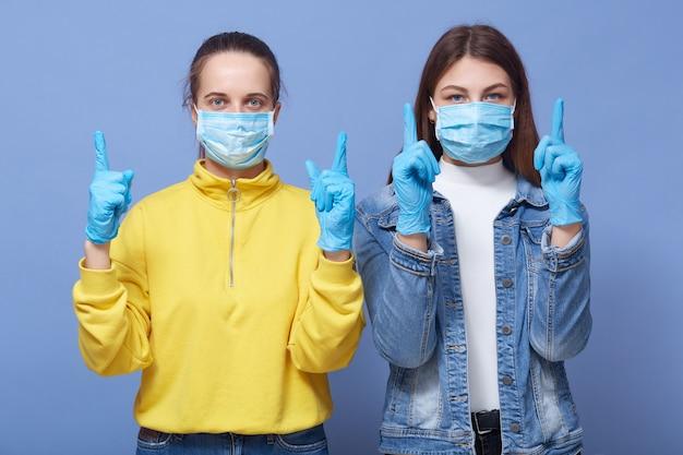 Feche o retrato de duas mulheres vestindo roupas casuais e máscaras de saúde