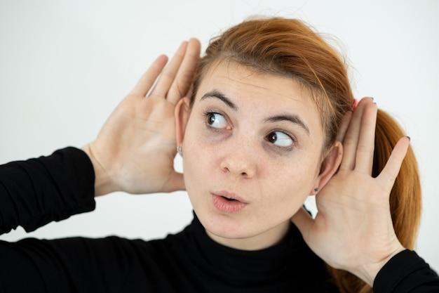 Feche o retrato de engraçadinha, segurando seus ouvidos com as mãos como um macaco.