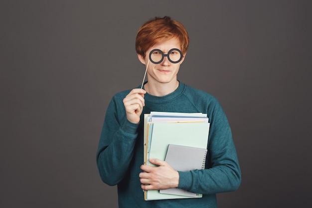 Feche o retrato de engraçado jovem ruivo bonitão na camisola verde segurando muitos cadernos na mão, olhando com expressão insegura através de óculos de festa de papel.