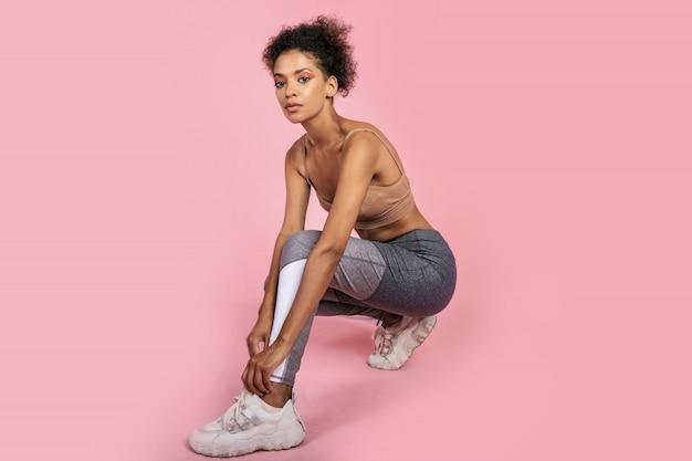 Feche o retrato de estúdio de linda mulher negra com cabelos afro, fazendo exercícios no estúdio em fundo rosa.
