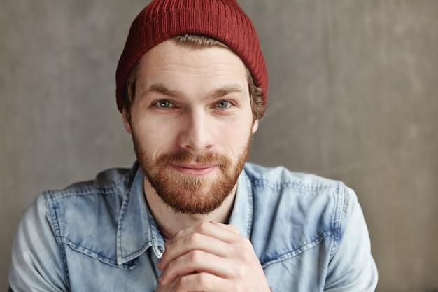 Feche o retrato de estúdio de um jovem europeu barbudo e elegante, usando chapéu e jaqueta jeans