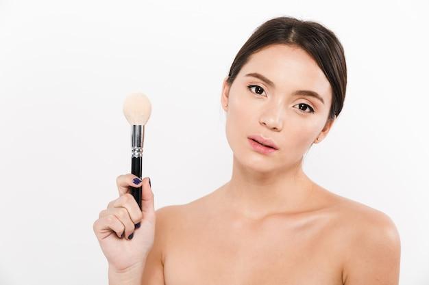 Feche o retrato de estúdio de uma linda mulher asiática com pele macia, segurando o pincel de maquiagem, isolado sobre o branco