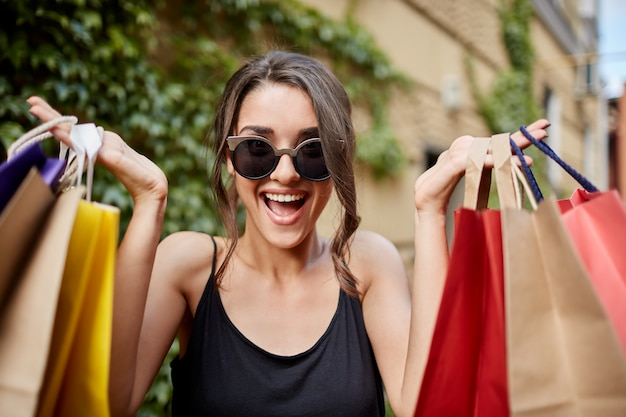 Feche o retrato de feliz alegre morena caucasiano em óculos de guia e camisa preta, olhando na câmera com a boca aberta e expressão feliz, segurando sacolas coloridas nas mãos. gi