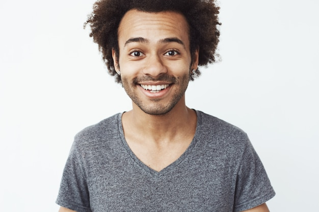 Feche o retrato de feliz e charmoso cara africana sorrindo, um namorado esperando uma data ou um sonho de caçador de cabeça em pé sobre uma parede branca.