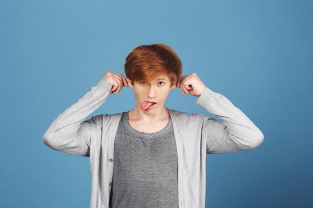 Feche o retrato de gengibre cara jovem bonita roupa casual cinza segurando os ouvidos com as mãos, mostrando a língua fazendo caretas durante a sessão de fotos de formatura.