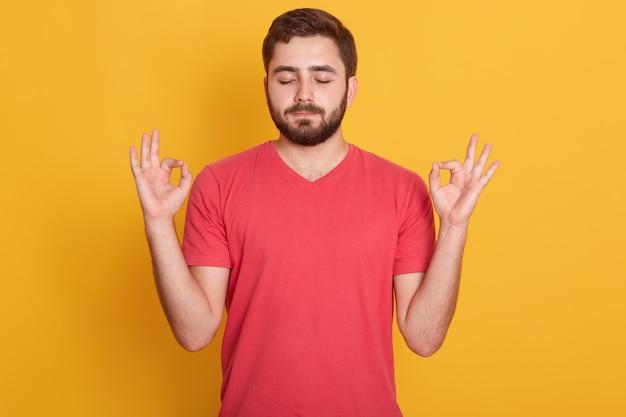 Feche o retrato de homem atraente veste camiseta casual vermelha gesticulando sinal bem com os olhos fechados