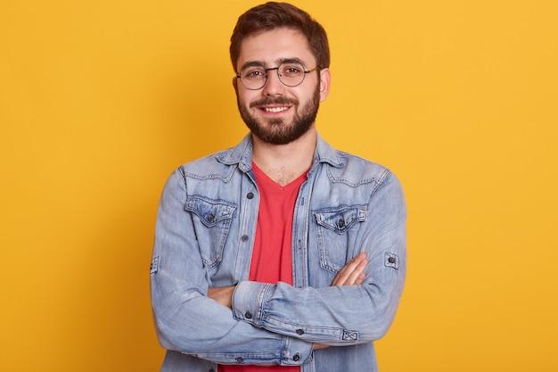 Feche o retrato de homem barbudo com as mãos postas, de pé e olhando diretamente para a câmera com expressão facial feliz, estar de bom humor, bonito macho vestido com roupas elegantes.