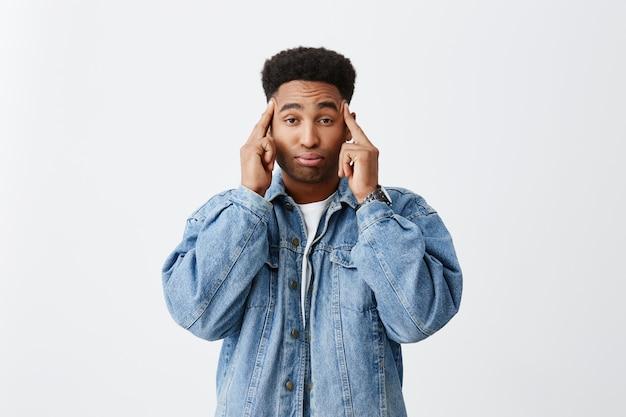 Feche o retrato de homens africanos de pele escura com penteado encaracolado em camiseta branca e jaqueta jeans, massageando a cabeça com os dedos, sendo estressado após um dia duro em estudo.