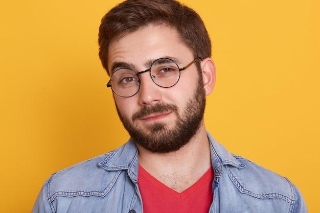 Feche o retrato de jovem bonito carismático, com barba, olhando diretamente, tendo feliz expressão facial